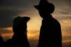 Jeunes couples dans l'amour sur des meules de foin dans des chapeaux de cowboy Images stock