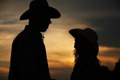 Jeunes couples dans l'amour sur des meules de foin dans des chapeaux de cowboy Image stock