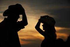 Jeunes couples dans l'amour sur des meules de foin dans des chapeaux de cowboy Photos stock