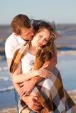 Jeunes couples dans l'amour sur la plage enveloppée dans une couverture Images stock