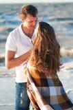 Jeunes couples dans l'amour sur la plage enveloppée dans une couverture Photos stock