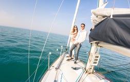 Jeunes couples dans l'amour sur le bateau à voile ayant l'amusement avec le champagne Photographie stock