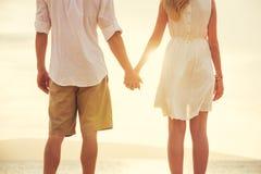 Jeunes couples dans l'amour sur le coucher du soleil de plage Image stock