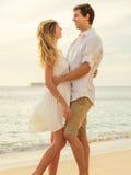 Jeunes couples dans l'amour sur le coucher du soleil de plage Photographie stock libre de droits