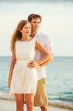 Jeunes couples dans l'amour sur le coucher du soleil de plage Images libres de droits