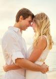 Jeunes couples dans l'amour sur le coucher du soleil de plage Photos libres de droits