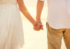 Jeunes couples dans l'amour sur le coucher du soleil de plage Photo libre de droits