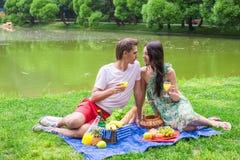 Jeunes couples dans l'amour sur un pique-nique dehors Photo stock