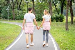 Jeunes couples dans l'amour tenant des mains et la marche photographie stock libre de droits