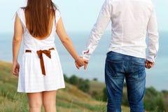 Jeunes couples dans l'amour tenant des mains. Fond de mer d'été Images libres de droits