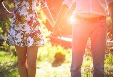 Jeunes couples dans l'amour tenant des mains sur le coucher du soleil Images libres de droits