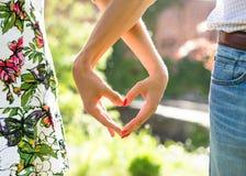 Jeunes couples dans l'amour tenant des mains sur le coucher du soleil pendant la soirée d'été Images stock