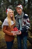 Jeunes couples dans l'amour utilisant des chapeaux de Santa, tenant a Image stock