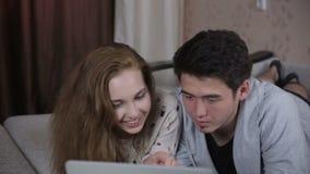 Jeunes couples dans l'amour utilisant l'ordinateur portable Technologie, famille, concept de commerce électronique banque de vidéos