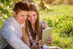 Jeunes couples dans l'amour utilisant un comprimé dans le jardin images libres de droits