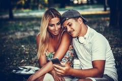 Jeunes couples dans l'amour utilisant un téléphone portable Image stock