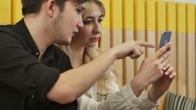 Jeunes couples dans l'Internet de lecture rapide de café au téléphone intelligent banque de vidéos