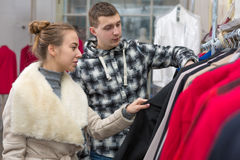 Jeunes couples dans la boutique d'habillement prenant la veste photos libres de droits
