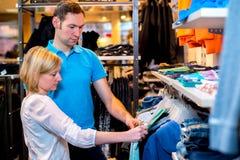 Jeunes couples dans la boutique de vêtements Image stock