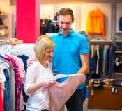Jeunes couples dans la boutique de vêtements Photos libres de droits