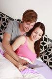 Jeunes couples dans la chambre à coucher avec l'ordinateur de comprimé Image libre de droits