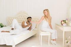 Jeunes couples dans la chambre à coucher, l'homme hispanique employant le lit menteur de téléphone intelligent de cellules et la  Photo stock