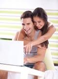 Jeunes couples dans la chambre à coucher utilisant l'ordinateur portable Images stock