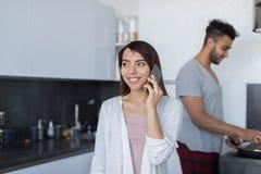 Jeunes couples dans la cuisine, appel téléphonique parlant de femme asiatique, homme hispanique faisant cuire le petit déjeuner Images stock