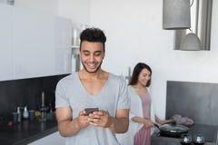 Jeunes couples dans la cuisine, femme asiatique faisant cuire le petit déjeuner de nourriture, homme hispanique à l'aide du télép Images stock