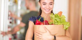 Jeunes couples dans la cuisine, femme avec un sac des achats d'épiceries Image stock