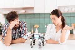 Jeunes couples dans la cuisine La fille gronde le type Entre eux est un rhinocéros de robot Images stock