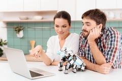 Jeunes couples dans la cuisine ils regardent quelque chose sur un ordinateur portable gris à côté de eux le robot est un rhinocér Photo libre de droits