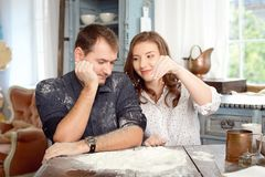 Jeunes couples dans la cuisine jouant avec de la farine Moments drôles, sourires, cuisson, heureuse ensemble, souvenirs Images stock