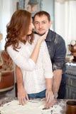 Jeunes couples dans la cuisine jouant avec de la farine Moments drôles, sourires, cuisson, heureuse ensemble, souvenirs Image stock