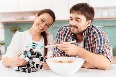 Jeunes couples dans la cuisine Le type et la fille alimentent le petit robot de rhinocéros Photographie stock libre de droits