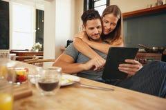Jeunes couples dans la cuisine rattrapant sur des mises à jour de matin Photographie stock