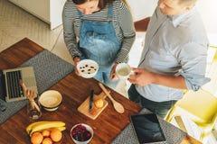 Jeunes couples dans la cuisson de cuisine L'homme est table proche debout et le thé potable, son épouse enceinte se tient à côté  Images libres de droits
