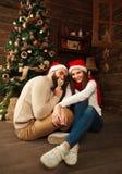 Jeunes couples dans la maison de vacances dans Noël célébrant ensemble Photographie stock libre de droits