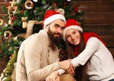 Jeunes couples dans la maison de vacances dans Noël célébrant ensemble Images stock