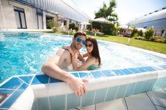 Jeunes couples dans la piscine image stock