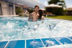 Jeunes couples dans la piscine photographie stock
