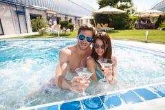 Jeunes couples dans la piscine photographie stock libre de droits