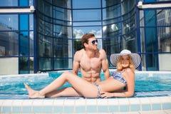 Jeunes couples dans la piscine photos stock