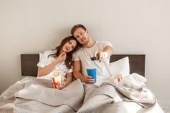 Jeunes couples dans le bâti Le beaux homme et femme de sourire jugent à télécommande et manger du maïs éclaté tout en regardant l photographie stock libre de droits