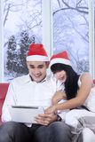 Jeunes couples dans le chapeau de Santa utilisant le comprimé Photos libres de droits
