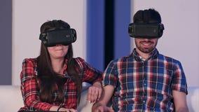 Jeunes couples dans le film de observation de casque de vr se reposant sur un sofa