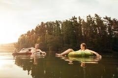 Jeunes couples dans le lac sur l'anneau gonflable Photographie stock libre de droits
