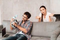Jeunes couples dans le salon Le type tient un robot La fille à côté de lui, elle est très malheureuse Photos stock