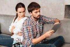 Jeunes couples dans le salon Le type tient un robot La fille à côté de lui, elle est très malheureuse Photos libres de droits
