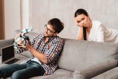 Jeunes couples dans le salon Le type tient un robot La fille à côté de lui, elle est très malheureuse Images stock